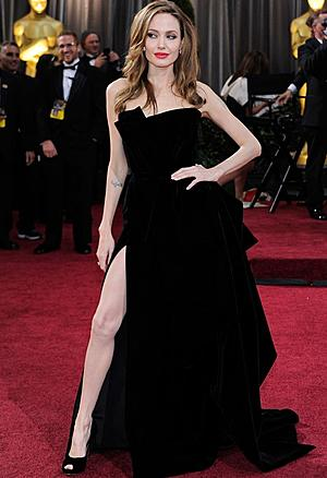 9a38c620d03a Angelina Jolie s black Atelier Versace gown (2012) remains memorable  because of the slit. She showed some serious leg. She looked hotter than a  furnace and ...