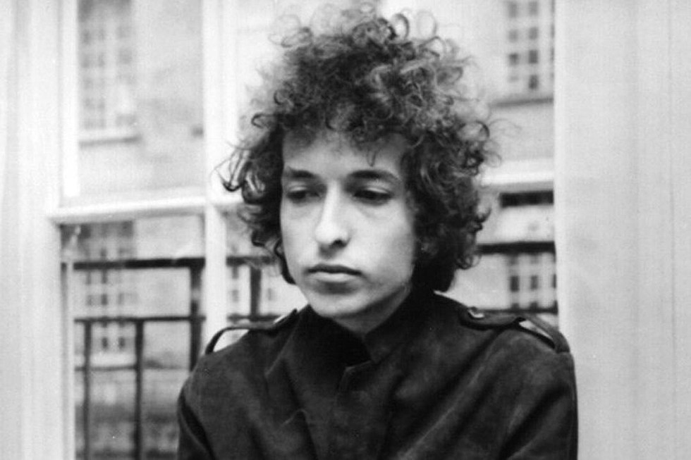 A black and white image of Bob Dylan looking downwards