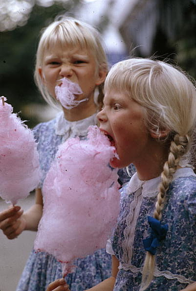 Girls eat large swirls of cotton candy | National Geographic/Getty Images