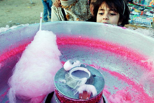 Girl waits for a serving of cotton candy - Getty Images