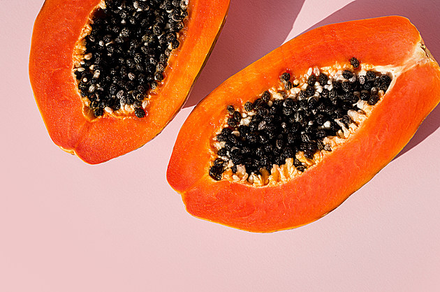 Fresh papaya exotic tropical fruit on pink background. Sun day light illumination. Minimalistic summer flat lay wallpaper. Creative food concept. Copy space template.