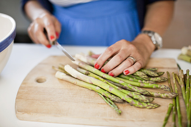 Close-up of woman chopping asparagus on cutting board